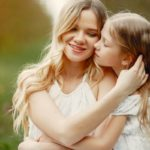 Pretty mother with daughter. Family in a spring park. Woman in a white dress